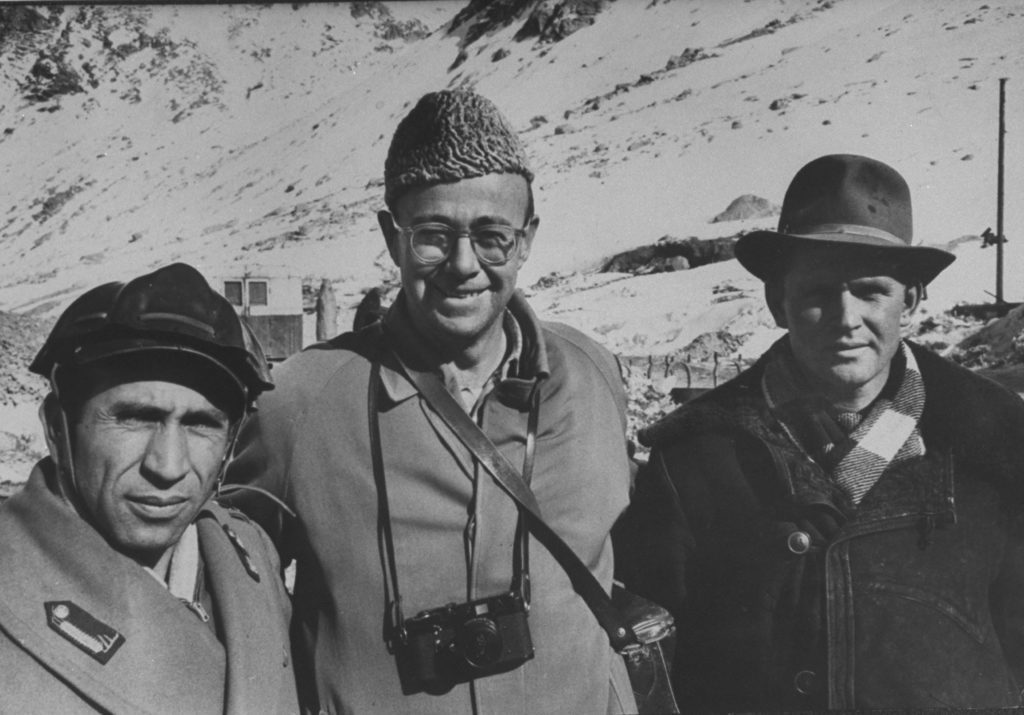 James Burke standing with friends and a camera around his neck. (Photo by James Burke/The LIFE Picture Collection © Meredith Corporation)