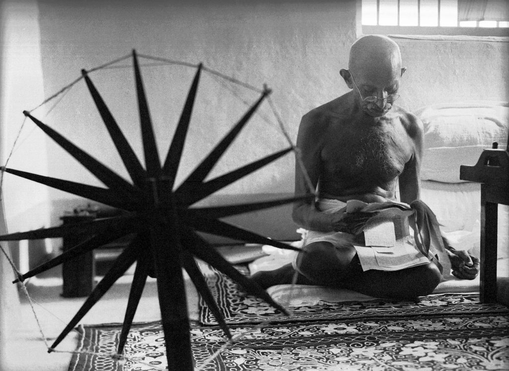 Indian leader Mohandas Gandhi reading next to a spinning wheel at home. (Photo by Margaret Bourke-White/The LIFE Picture Collection © Meredith Corporation)