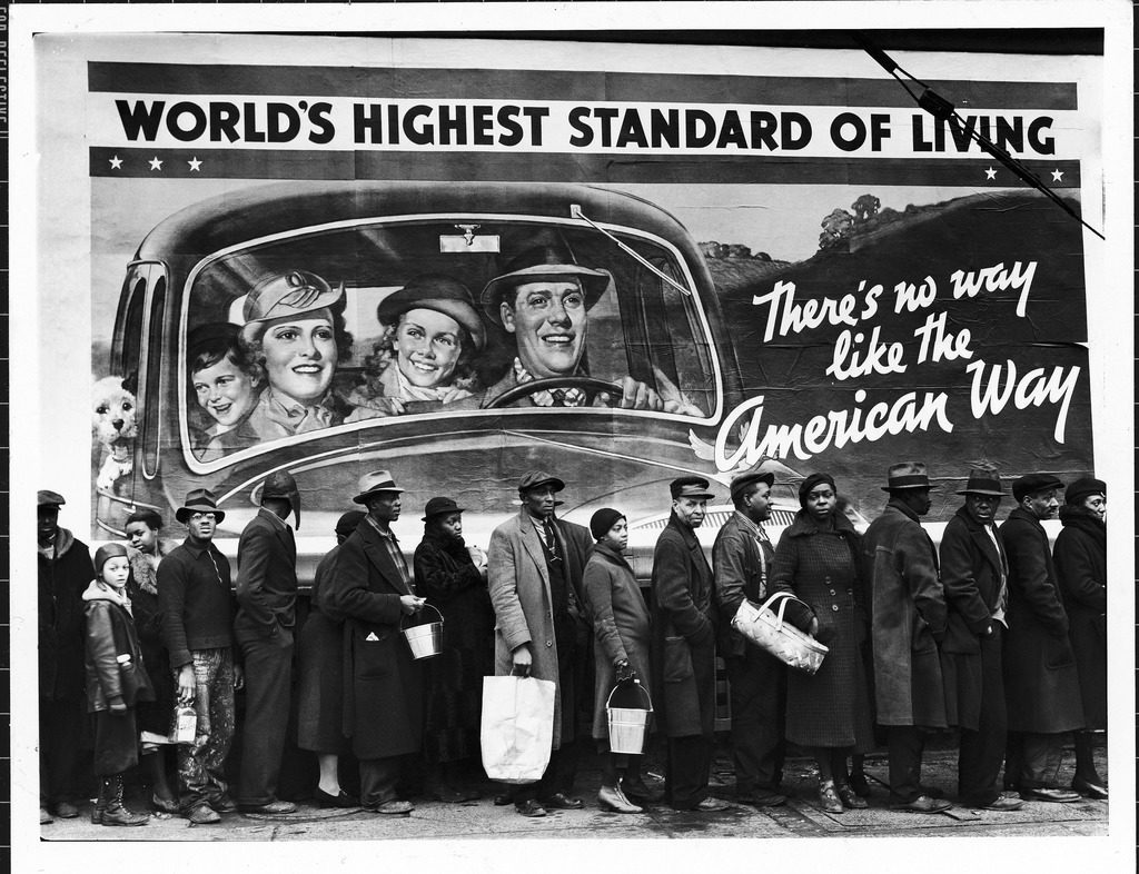 """African American flood victims lined up to get food and clothing from a Red Cross relief station in front of an ironic billboard extolling, """"World's highest standard of living/ there's no way like the American way."""" (Photo by Margaret Bourke-White/The LIFE Picture Collection © Meredith Corporation)"""