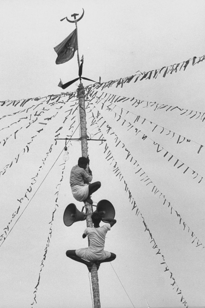 Communist workers fixing loudspeaker on a stripped coconut tree during the Travancore-Cochin elections. (Photo by James Burke/The LIFE Picture Collection © Meredith Corporation)