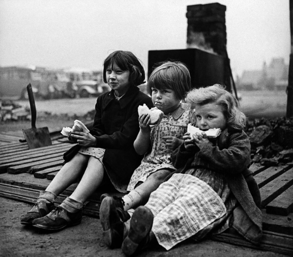 Children in blitzed north of England eating meal from bread and Lease Lend cheese. (Photo by Hans Wild/The LIFE Picture Collection © Meredith Corporation)