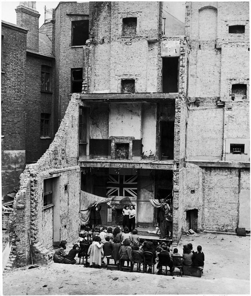Children in Aldgate using the ruins of a bombed house as a stage for a vaudeville show. (Photo by Hans Wild/The LIFE Picture Collection © Meredith Corporation)