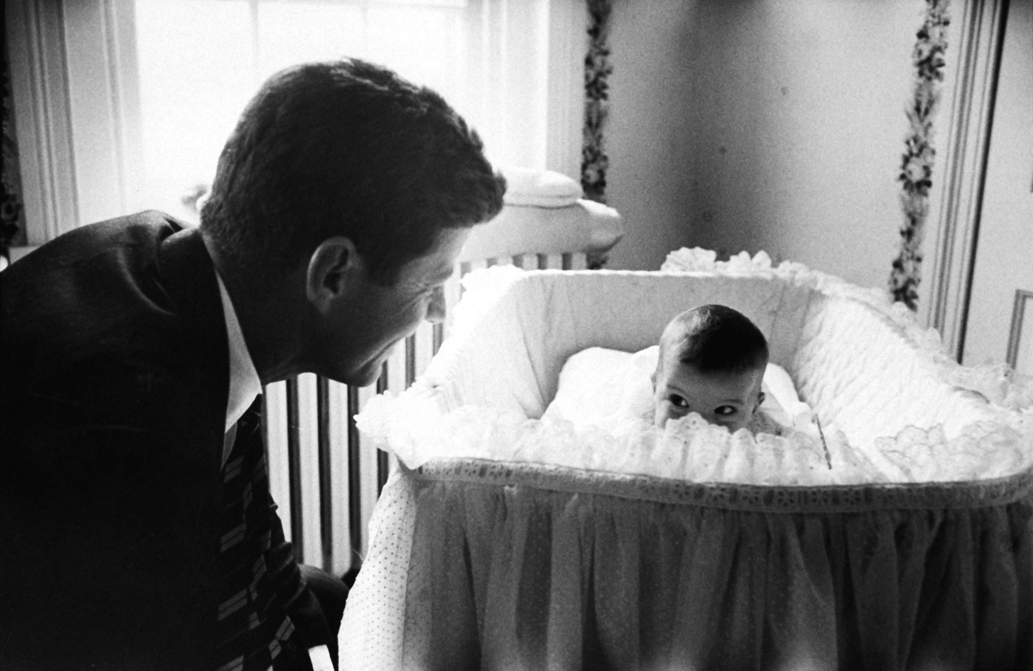 Senator John F. Kennedy playing peek-a-boo with his daughter Caroline in her crib. (Photo by Edward Clark/The LIFE Picture Collection © Meredith Corporation)