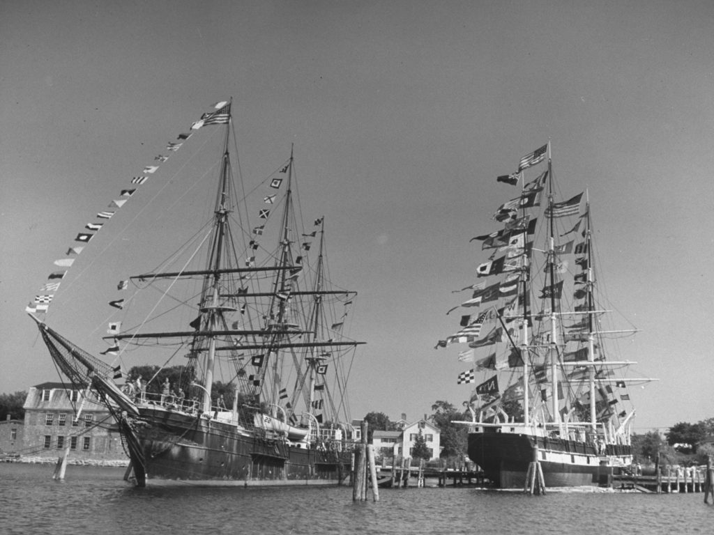 The sailing ship the Joseph Conrad (L) and the whaler Charles W. Morgan (R), both adorned with many flags. (Photo by Sam Shere/The LIFE Picture Collection © Meredith Corporation)