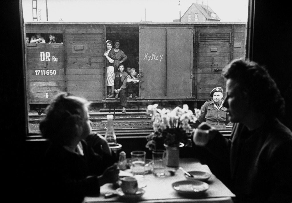 "Wife and daughter of a US soldier sitting in a first class dining car looking out at German ""expels"" travelling in boxcars. (Photo by Walter Sanders/The LIFE Picture Collection © Meredith Corporation)"