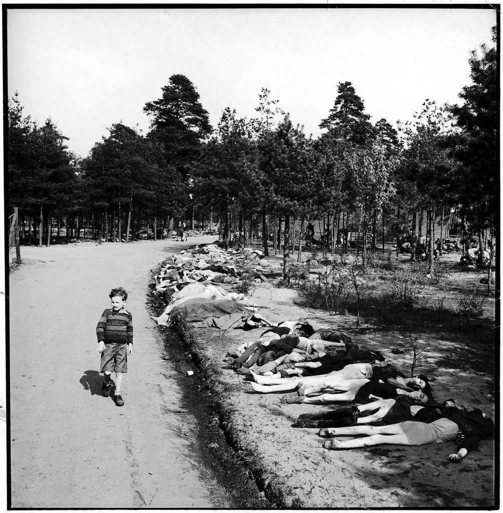 German boy walking down a dirt road lined with the corpses of hundreds of prisoners who have died of starvation near Bergen extermination camp.(Photo by George Rodger/The LIFE Picture Collection © Meredith Corporation)