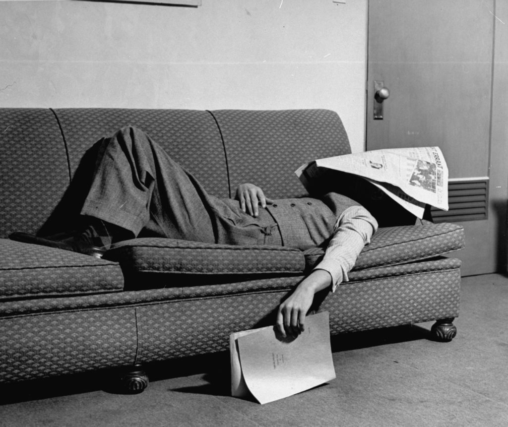 Writer Niven Busch lying on sofa with newspaper over his face as he takes nap from screenwriting. (Photo by Paul Dorsey/The LIFE Picture Collection © Meredith Corporation)