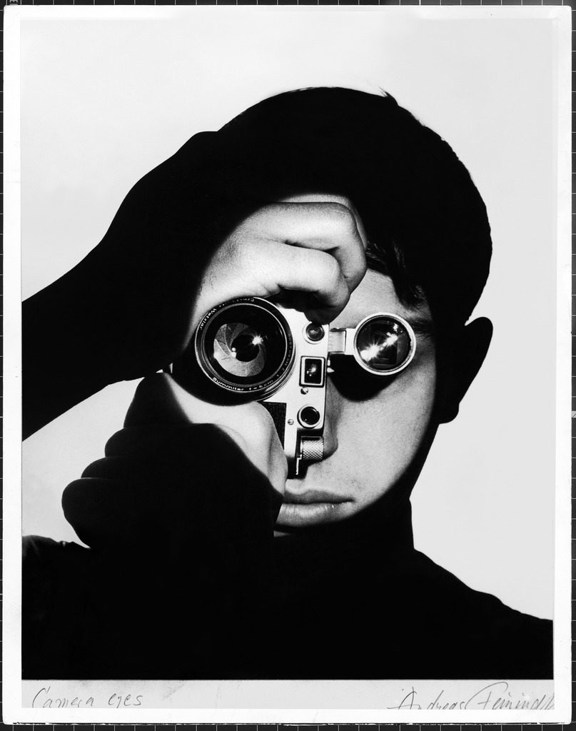 Photographer Dennis Stock holding camera to his face so that the lens looks like his right eye and the viewfinder his left eye. (Photo by Andreas Feininger/The LIFE Picture Collection © Meredith Corporation)