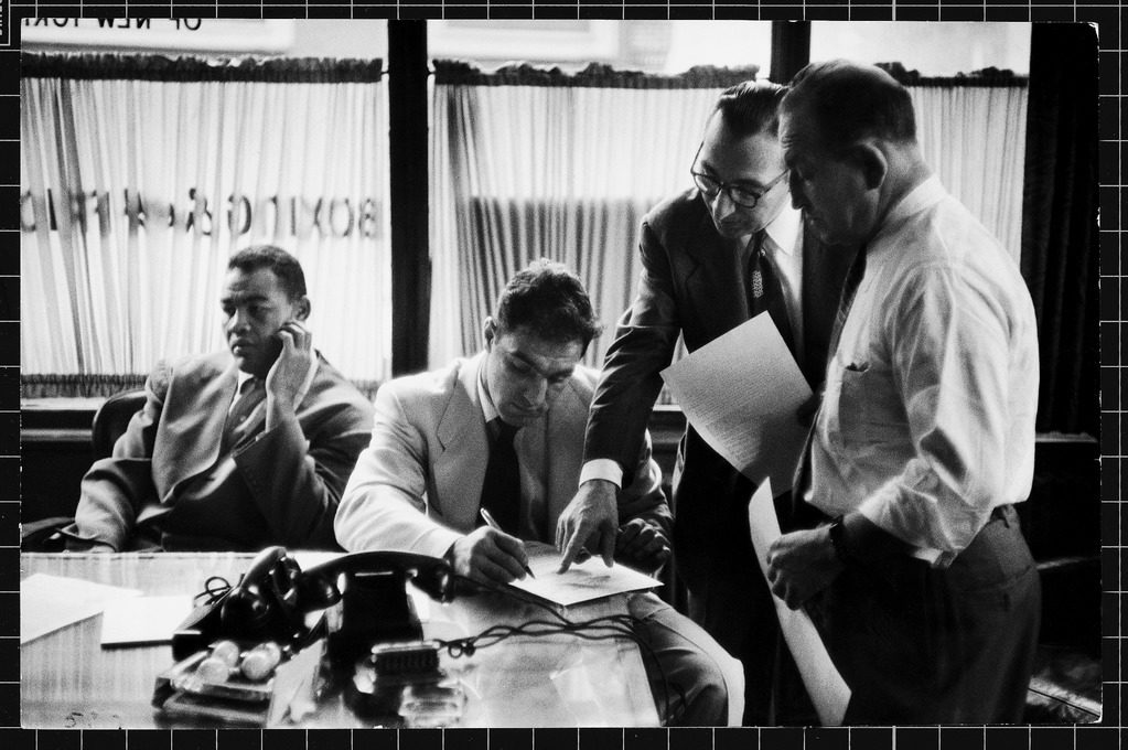 Boxer Rocky Marciano (seated R) signing a contract for a fight while Joe Louis (seated L) looks the other way. (Photo by Al Fenn/The LIFE Picture Collection © Meredith Corporation)