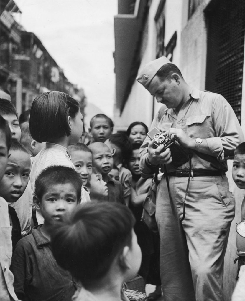 Photographer John Florea surrounded by Chinese children in a Queen's Road marketplace. (Photo by John Florea/The LIFE Picture Collection © Meredith Corporation)