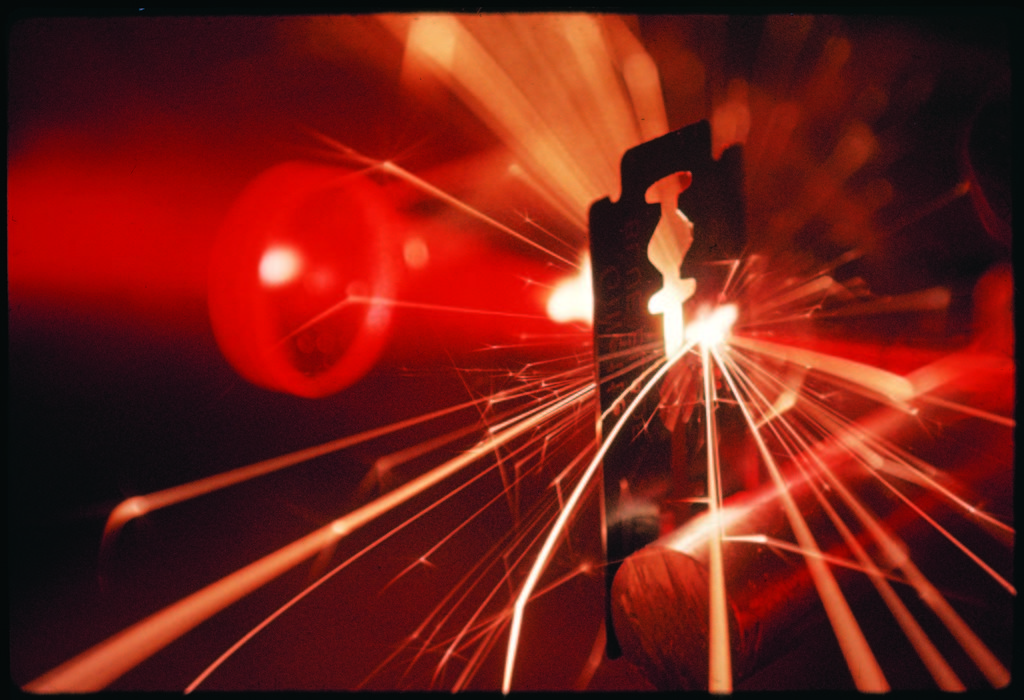Red laser light focused through a lens blasts a pin-point hole through a razor blade in a thousandth of a second. (Photo by Fritz Goro/The LIFE Picture Collection © Meredith Corporation)