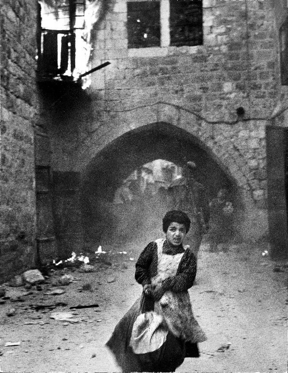 Terrified young Jewish girl Rachel Levy, 7, fleeing from a street with burning buildings as the Arabs sack the Holy City after its surrender during Palestinian Civil war. (Photo by John Phillips/The LIFE Picture Collection © Meredith Corporation)