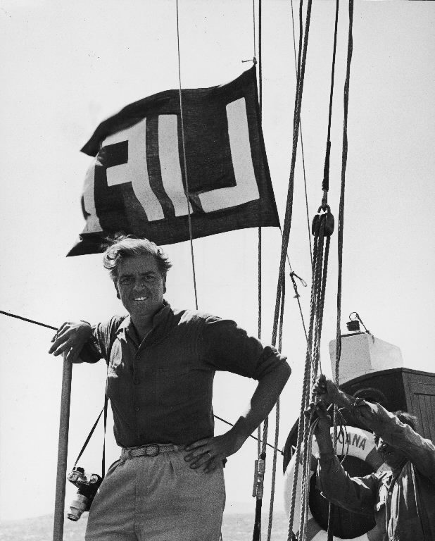Photographer John Phillips aboard boat posing in front of LIFE flag he hoisted in hopes of getting pictures of a Greek royal cruise from which press was barred. (Photo by John Phillips/The LIFE Picture Collection © Meredith Corporation)