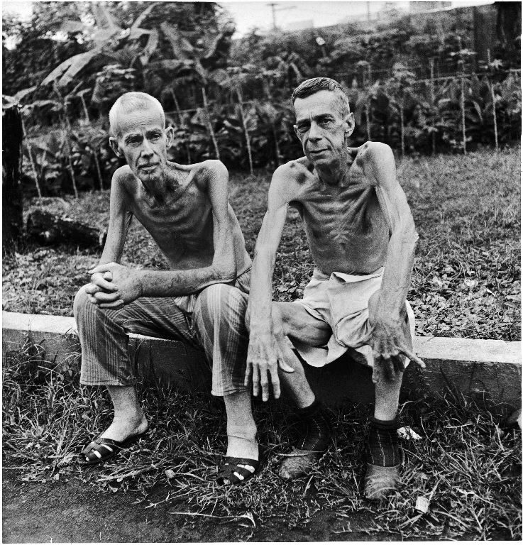 Two emaciated American civilians, Lee Rogers (L) and John C. Todd, sitting outside a Japanese prison camp following their release by Allied forces liberating the city. (Photo by Carl Mydans/The LIFE Picture Collection © Meredith Corporation)