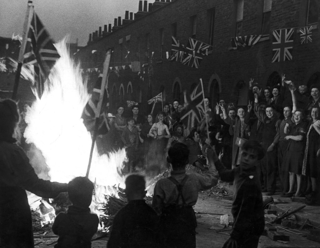 A crowd of joyous Britons wave flags around a bonfire built of material from bomb-wrecked homes as they celebrate the end of WWII in Europe following the surrender of Germany, London, England, May 8, 1945. (Photo by Leonard McCombe/The LIFE Images Collection)