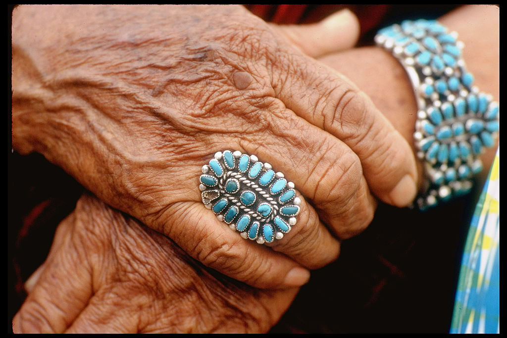 Closeup of beautifully weathered hands of Navajo woman modeling turquoise bracelet & ring made by Native Americans. (Photo by Michael Mauney/The LIFE Picture Collection © Meredith Corporation)