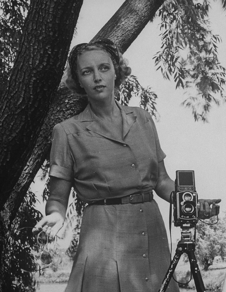 Photographer Nina Leen holding shutter release, standing beside her Rolleiflex, which is set up on tripod. (Photo by Time Life Pictures/Pix Inc./The LIFE Picture Collection © Meredith Corporation)