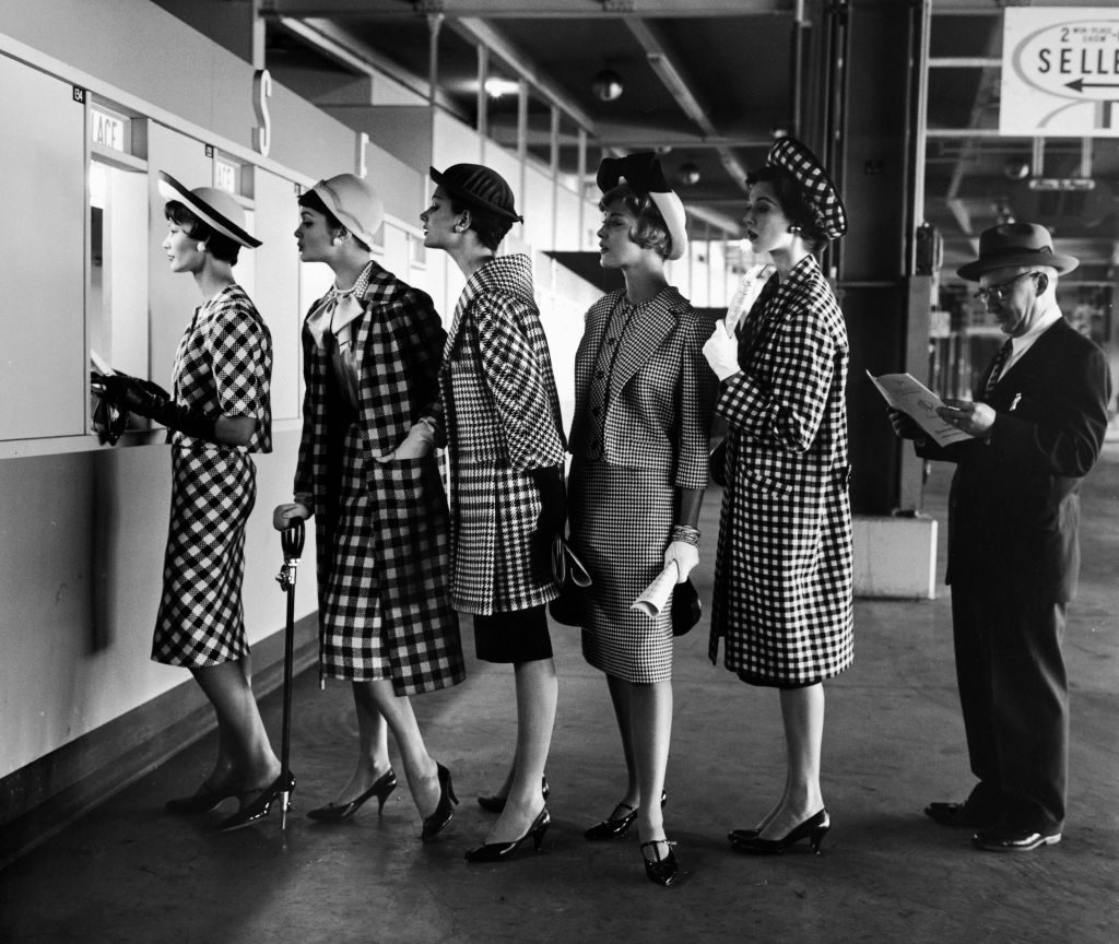 5 models wearing fashionable dress suits at a race track betting window, at Roosevelt Raceway. (Photo by Nina Leen/The LIFE Picture Collection © Meredith Corporation)
