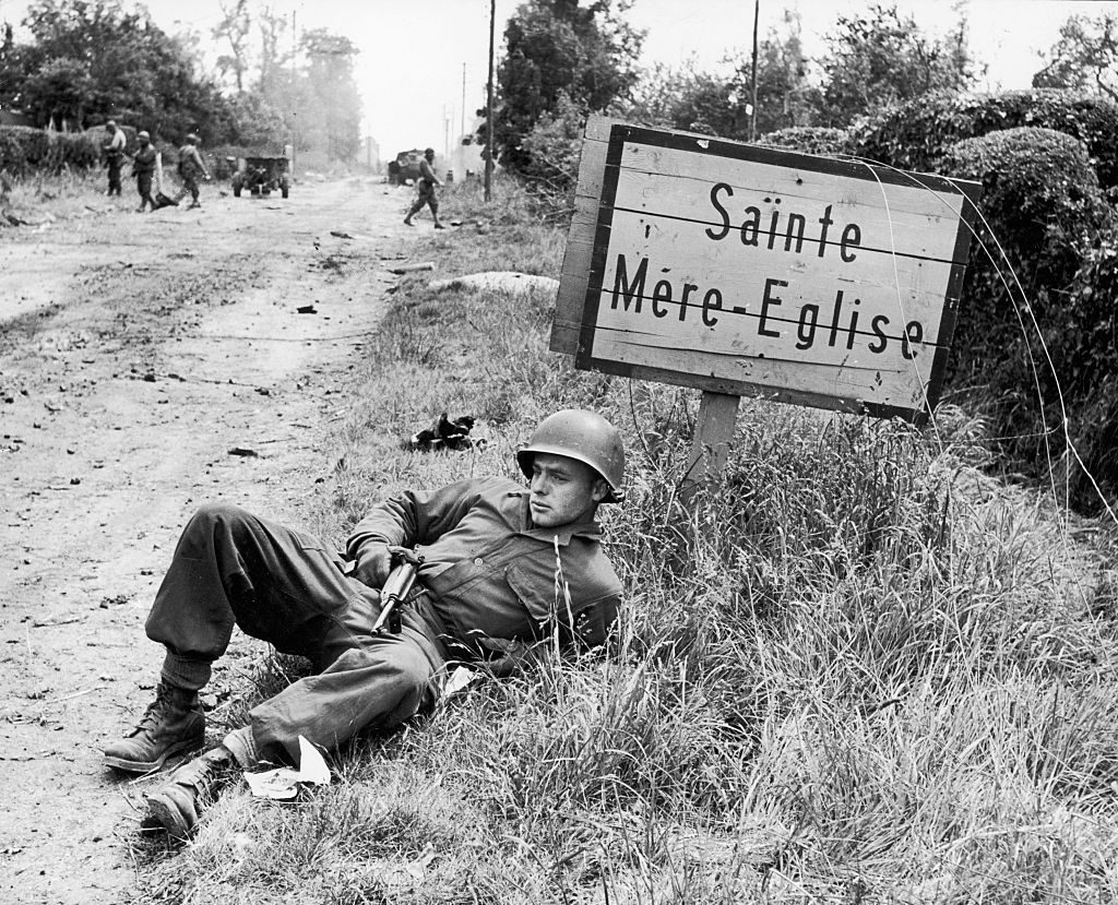 American soldier Elmer Habbs of Delaware resting next to signpost for the French town of Ste. Mere-Eglise as troops advance on the 2nd day of the Allied invasion of Normandy. (Photo by Bob Landry/The LIFE Picture Collection via © Meredith Corporation)