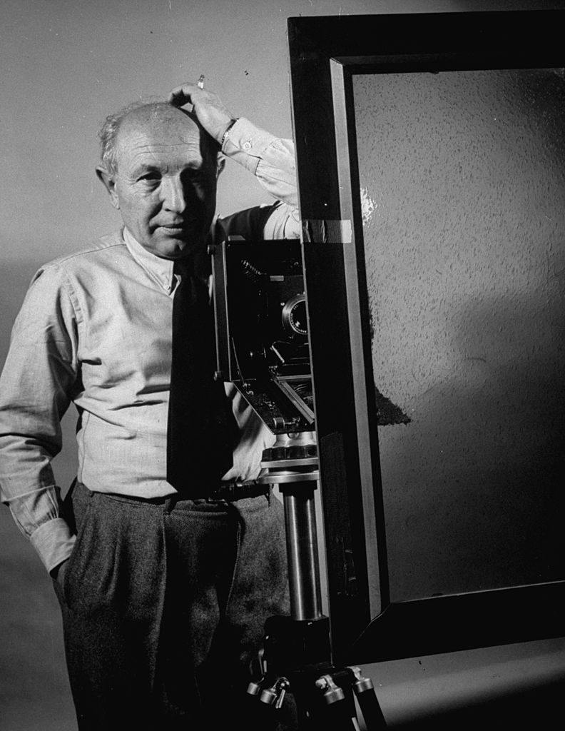 Life photographer, Dmitri Kessel, standing by camera on a tripod, getting ready to shot a picture of himself through a reflection in a make-shift window. (Photo by Frank Scherschel/The LIFE Picture Collection © Meredith Corporation)