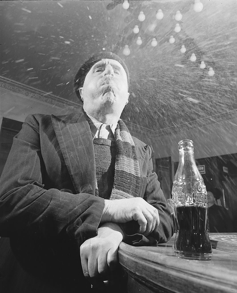 At a bar, a man in a beret spits a mouthful of Coca-Cola at the camera, Paris, France, April 1950. (Photo by Mark Kauffman/The LIFE Picture Collection © Meredith Corporation)