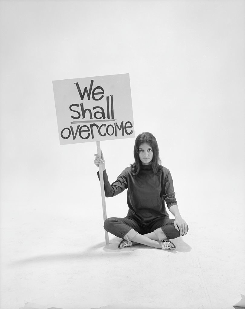 Writer Gloria Steinem sitting cross-legged on floor w. sign We Shall Overcome re pop culture (Photo by Yale Joel/The LIFE Picture Collection © Meredith Corporation)