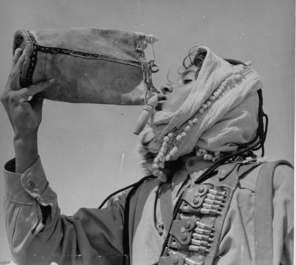 An Arabian showing off his head-dress while taking a drink of water. (Photo by James Jarche/The LIFE Picture Collection © Meredith Corporation)