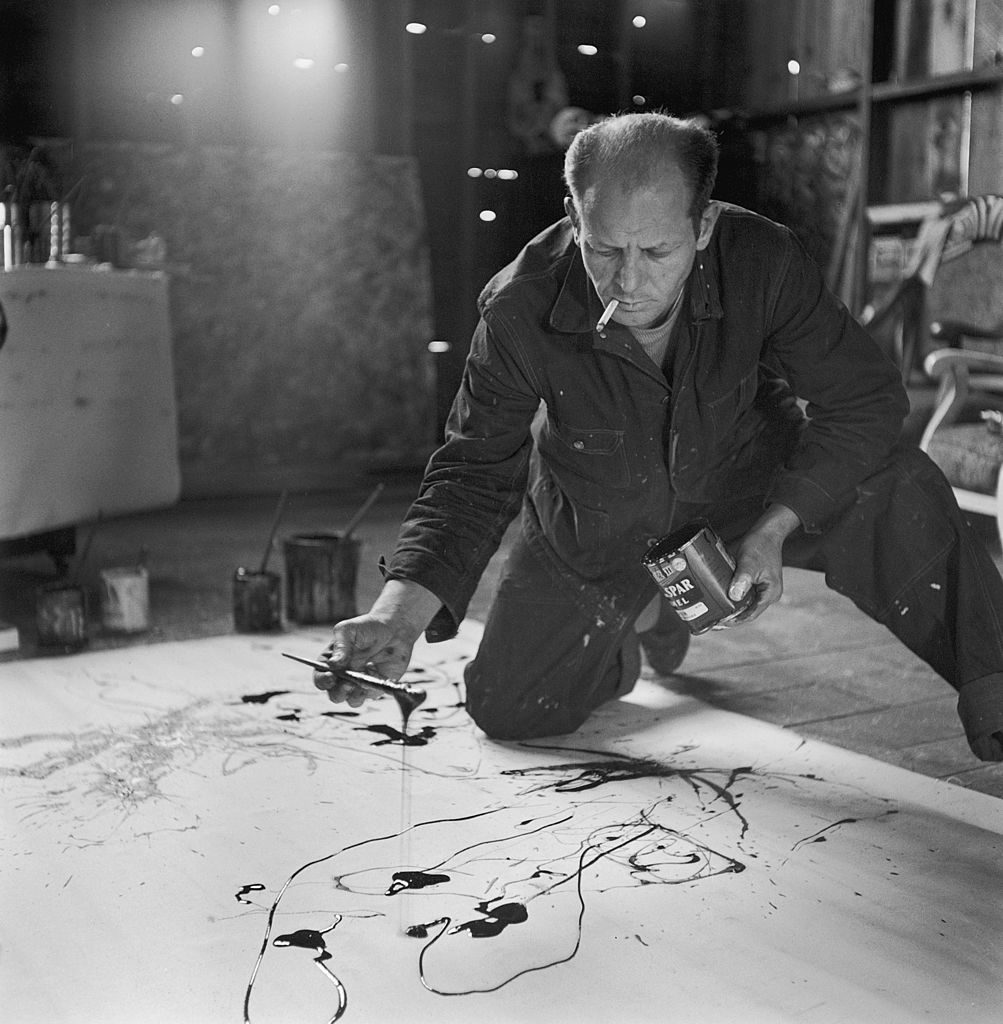 Painter Jackson Pollock smoking as he squats on floor, applying paint to canvas in Long Island studio. (Photo by Martha Holmes/The LIFE Picture Collection © Meredith Corporation)