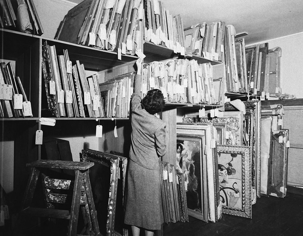 An unidentified woman looks at the tag on one of many paintings in a storage room in the home of financier and art collector Chester Dale, New York, New York, 1938. (Photo by Rex Hardy/The LIFE Picture Collection © Meredith Corporation)