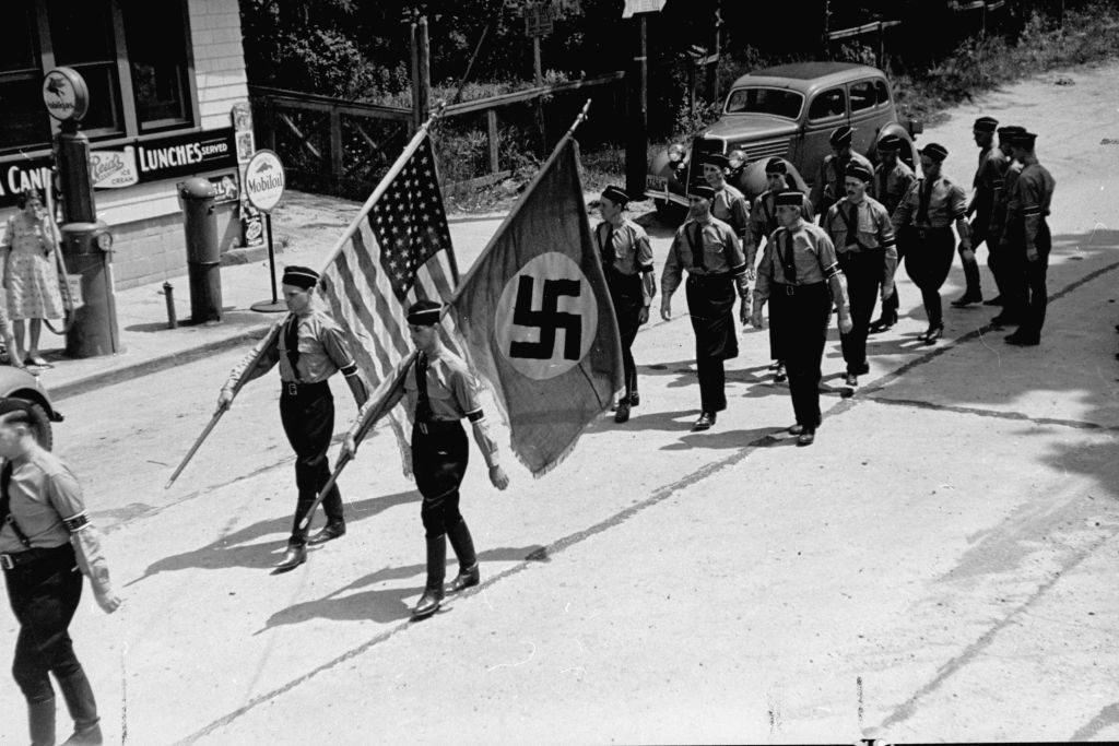 American Nazi party members, (aka German American Bund) march while carrying Nazi and American flags during a Bund outing from nearby Camp Sigfried. (Photo by Rex Hardy/The LIFE Picture Collection © Meredith Corporation)