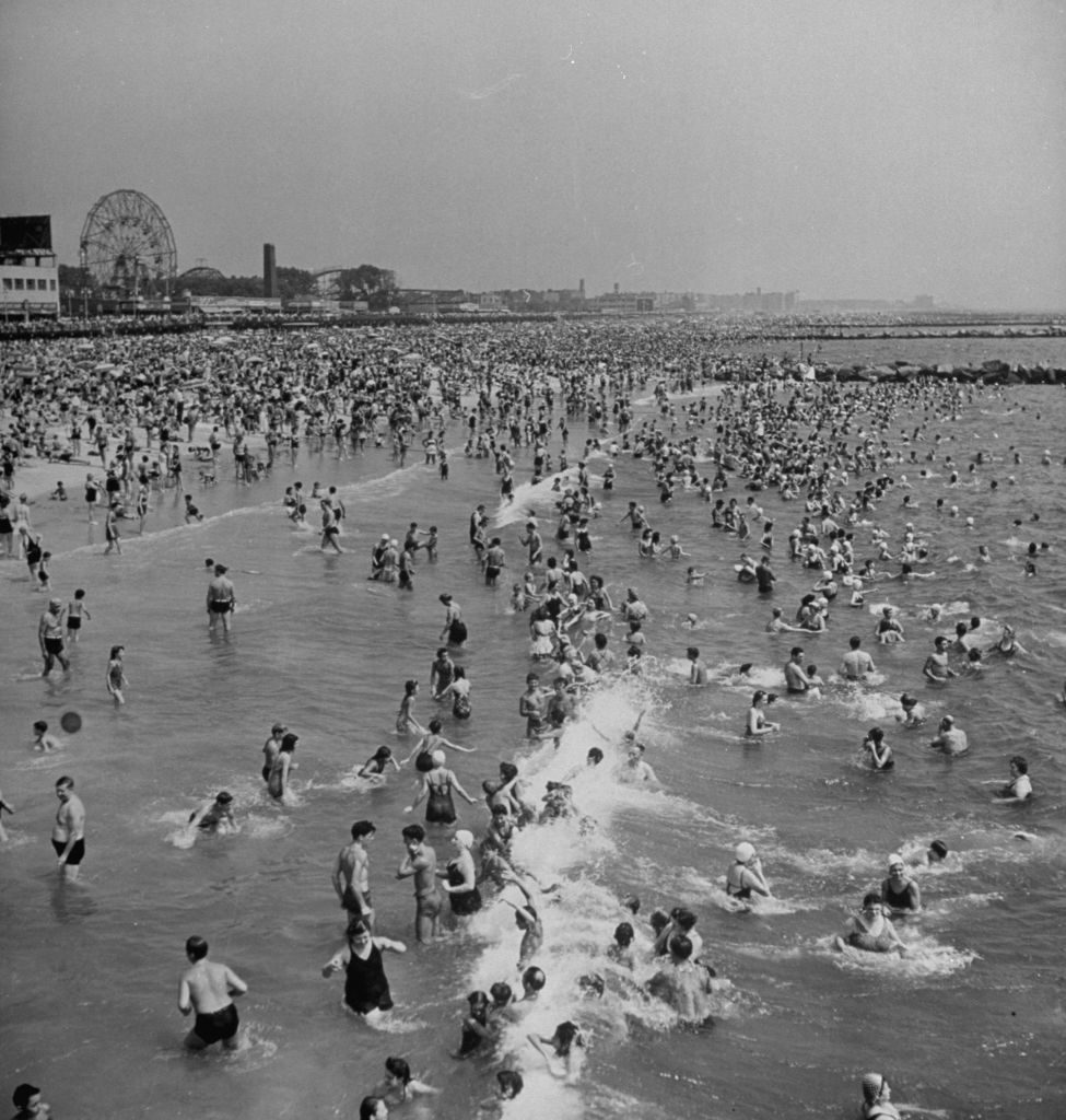 Huge crowd gathered in the surf and amp; at the beach in front of Coney Island Amusement Park. (Photo by Marie Hansen/The LIFE Picture Collection © Meredith Corporation)