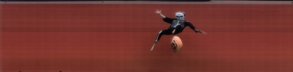 Child in Halloween skeleton costume jumping in air.