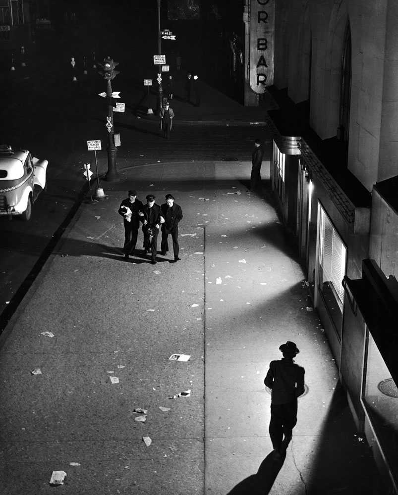 A trio of sailors walk arm in arm down a dimly lit street near Times Square, searching vainly for fun in the curfew-quiet city, February 1945.