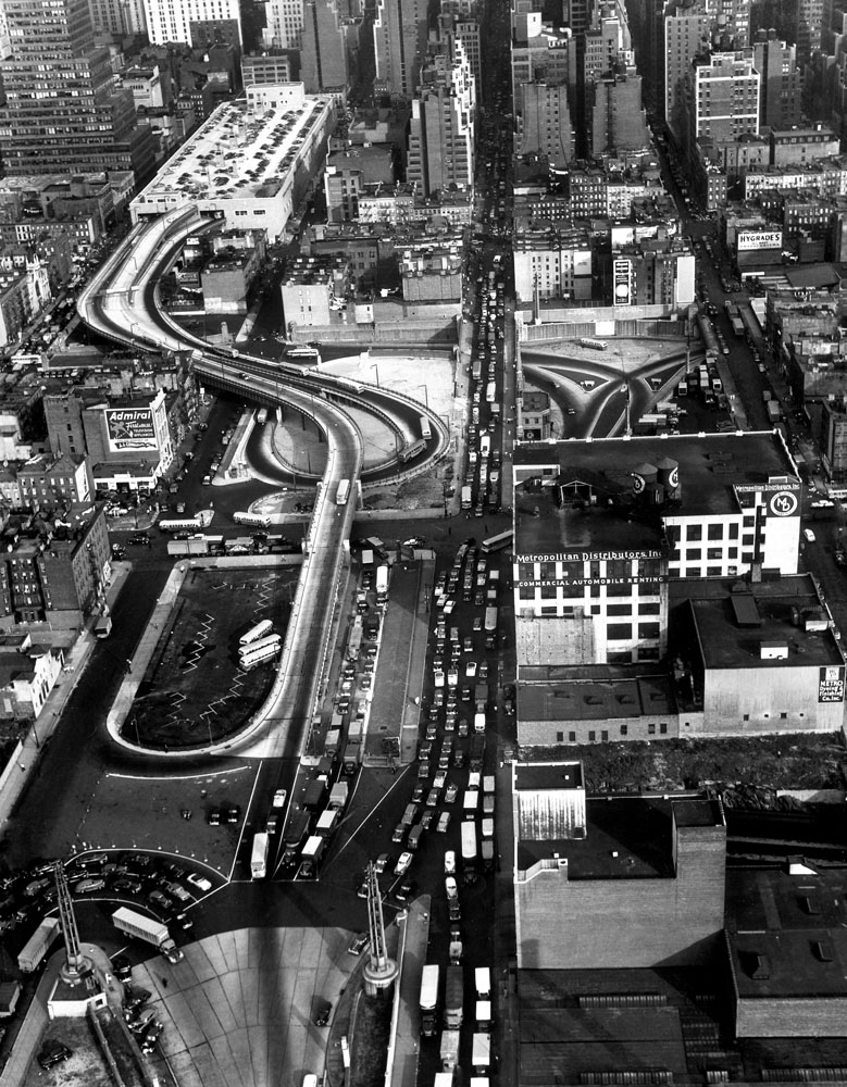 An aerial view of the entrance ramp leading to the top of the Port Authority Bus Terminal against the skyline of New York City in 1950.