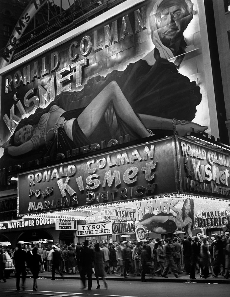 New Yorkers crowd Broadway below a large billboard depicting actress Marlene Dietrich in October 1944.