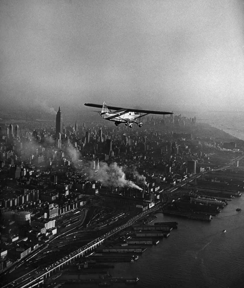 A plane flys above New York, NY before landing in October 1949.