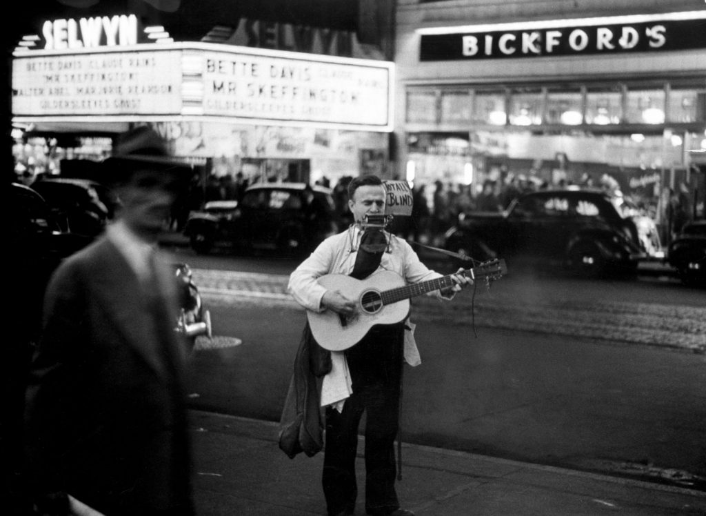 """A strolling blind musician plays guitar and harmonica along Broadway at night in the Times Square Area in 1944. """"Mr. Skeffington"""" is playing at the Selwyn Theater across the street."""