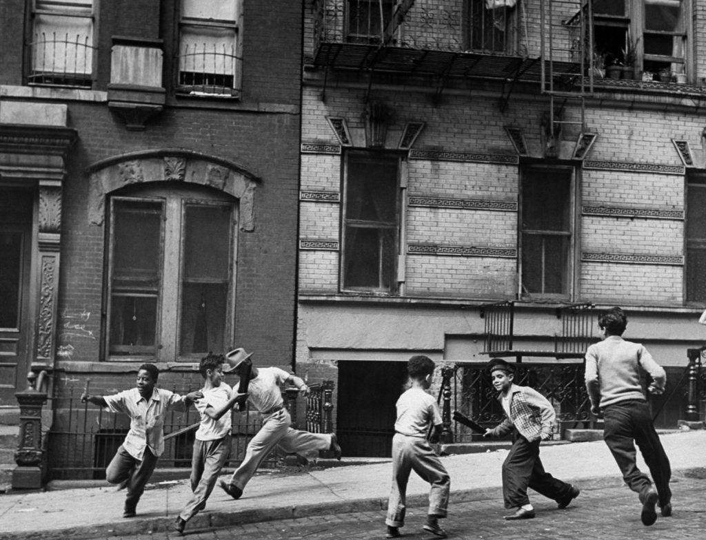 Young boys with sticks run around while playing a street game in Spanish Harlem in January 1947.