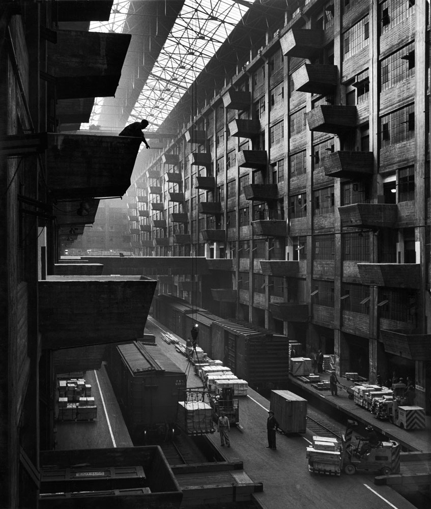 Off-loaded freight front box cars are hoisted up to jutting loading platforms at Brooklyn Army Terminal in October 1949.