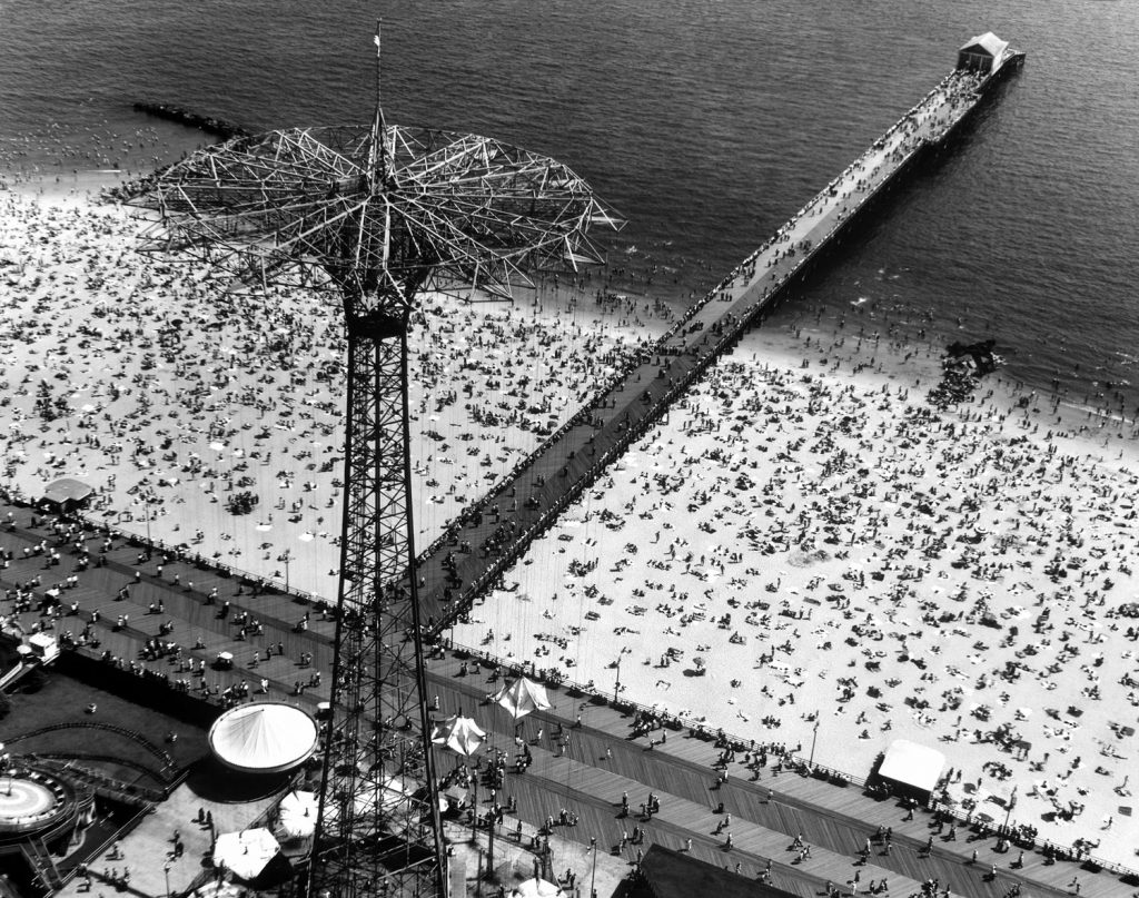 Aerial view of the crowded beach and pier at Coney Island, including the Parachute Jump amusement park ride (the tall structure at left) in Brooklyn, New York, 1951.