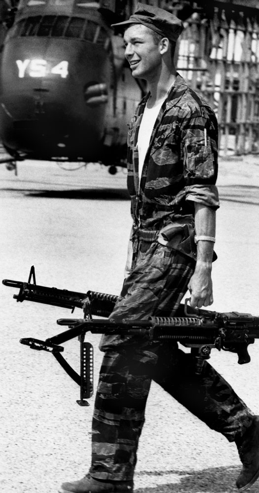 Yankee Papa 13 crew chief James Farley carries M-60 machine guns to the helicopter.