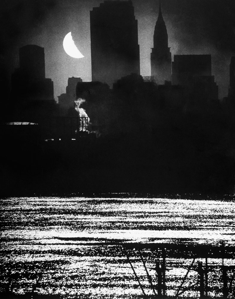 A view from New Jersey of the moon shining over Manhattan's RCA and Chrysler buildings as its light shimmers on the waters of the Hudson River in September 1946.