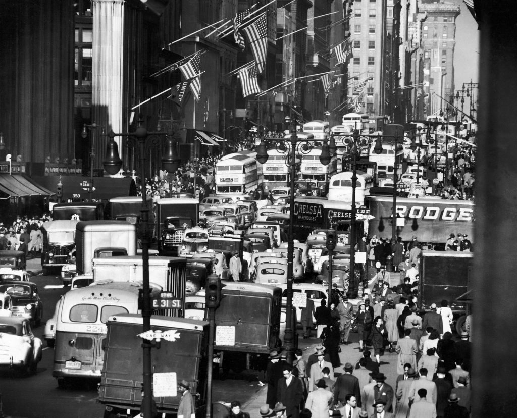 Pre-Christmas holiday traffic teaming with double-decker buses, trucks and cars, crawling along two-way-laned, 5th avenue near 34th street in November 1948.