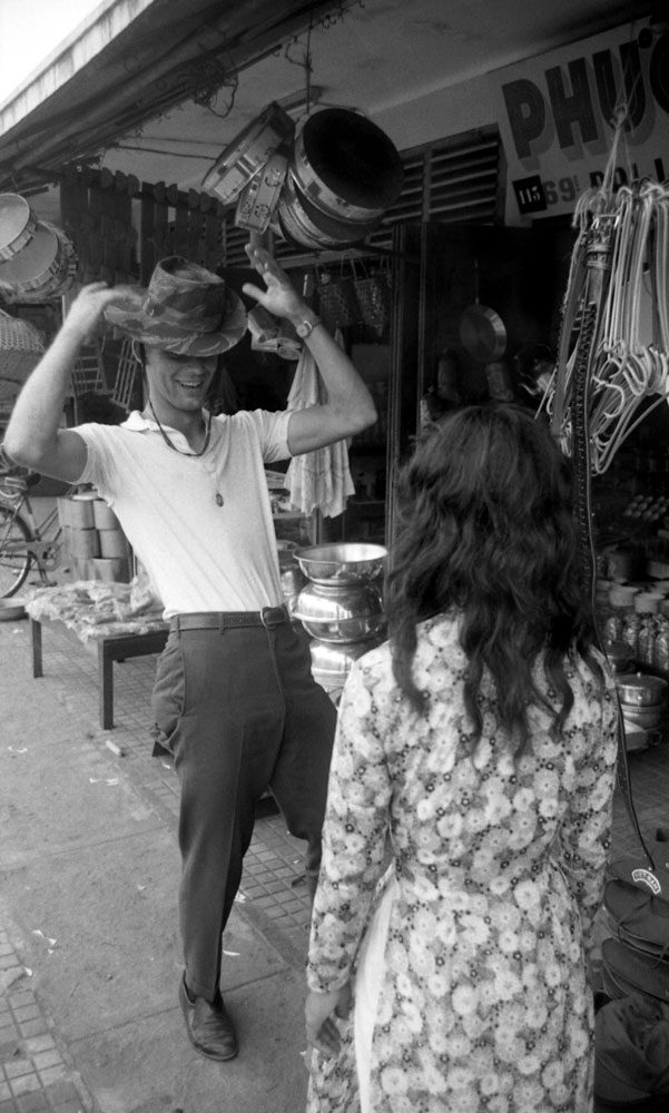 James Farley takes a fancy to a bush hat and models it in the street, Da Nang, March 1961.