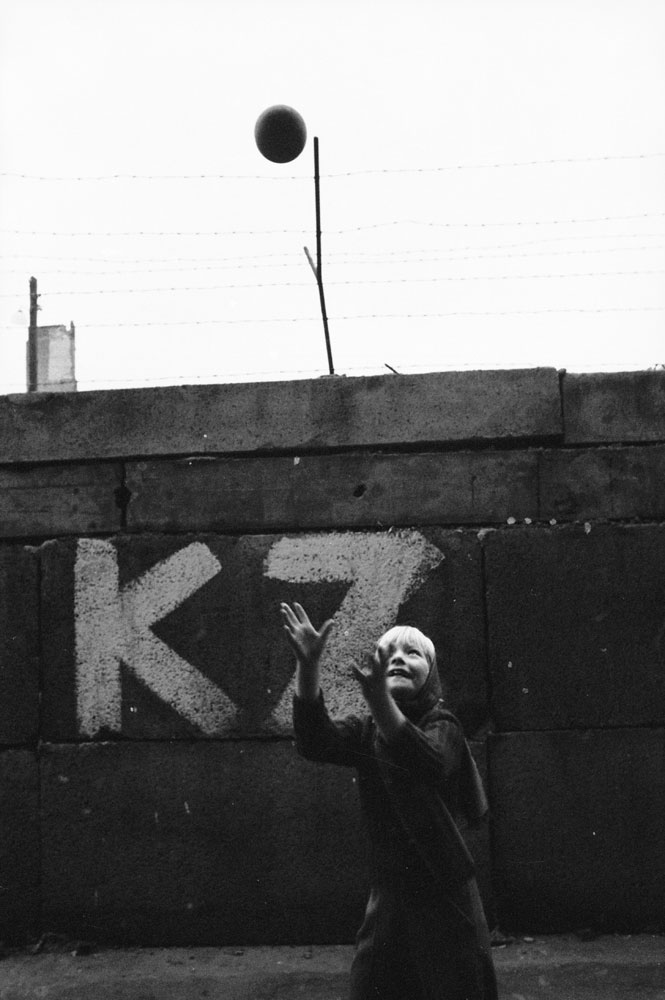 A girl plays with a ball at the Berlin Wall.