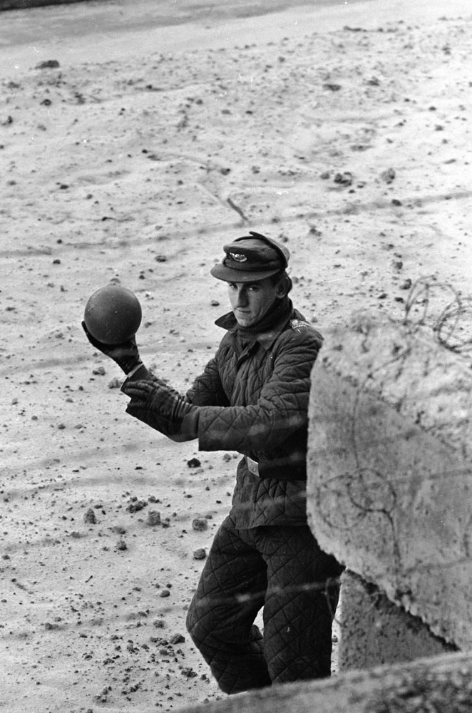 An East German guard throws a ball back to a child on the West German side of the Berlin Wall in 1962.
