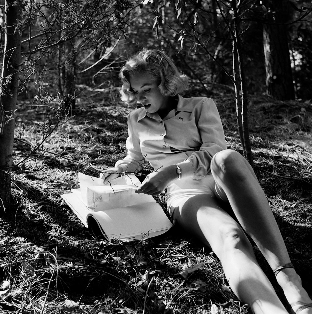 Marilyn Monroe reads a script in a park in Los Angeles.