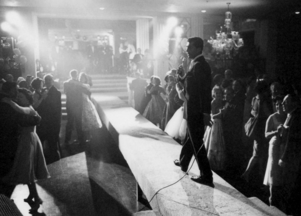 Dean Martin entertains on a narrow stage with couples dancing around him in 1958.