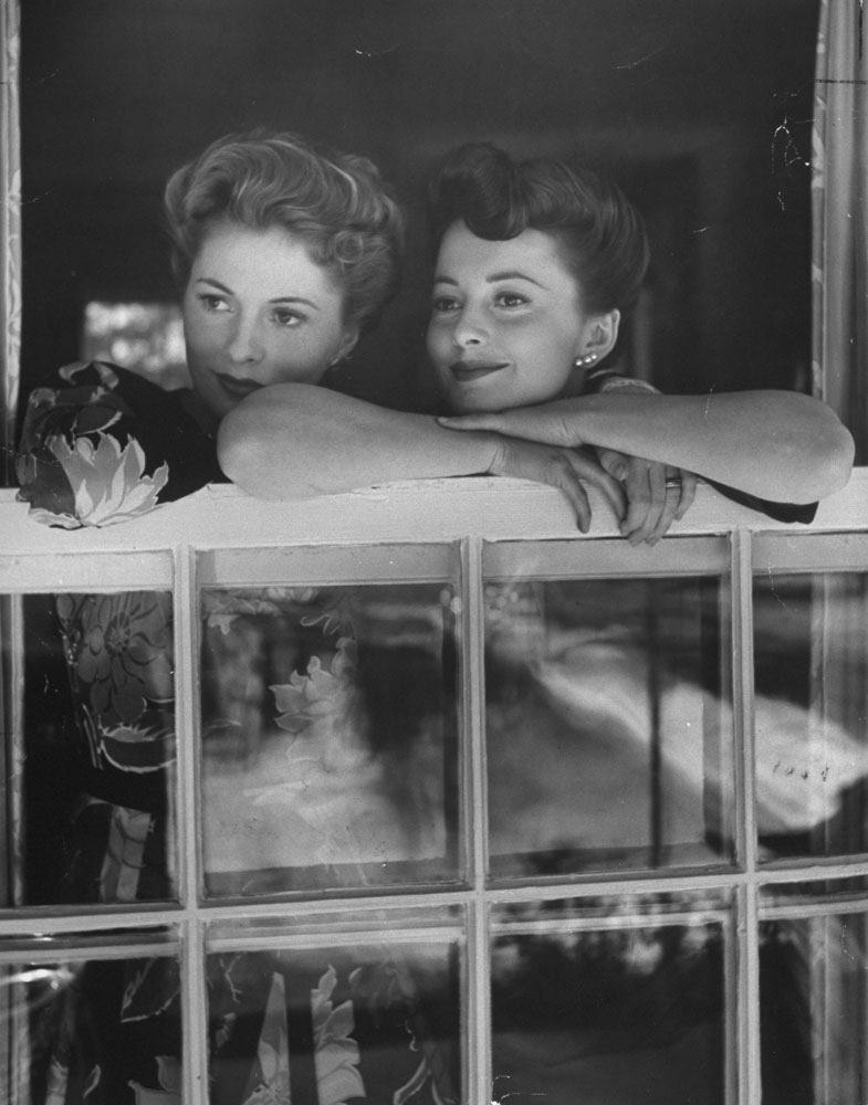 Joan Fontaine and Olivia de Havilland share a family moment as they look out over Beverly Hills from Fontaine's home in 1942.