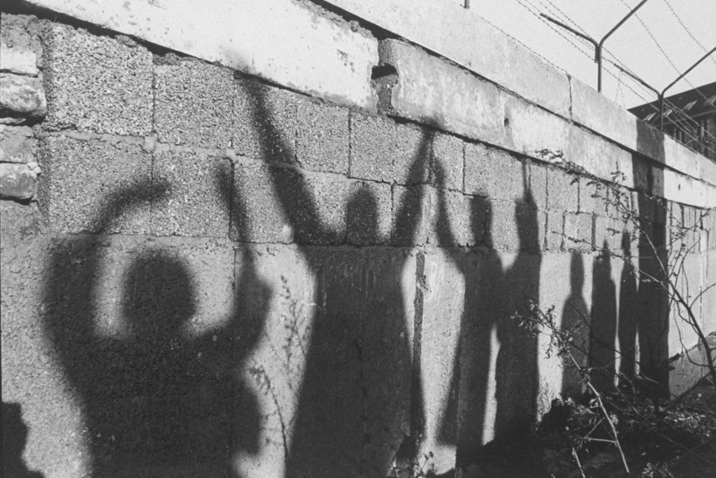 Silhouettes of West Berliners waving to their relatives on the other side are cast across the Berlin Wall.